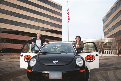 "(Left) Best Buy's Jason Pucely, senior manager of logistics & transportation, and Rosa Baumanis Hakala, VP, supply chain - transportation, stand with one of the ""GeekMobiles,""  a black and white Volkswagen Beetle, one of the key icons of the company's brand."