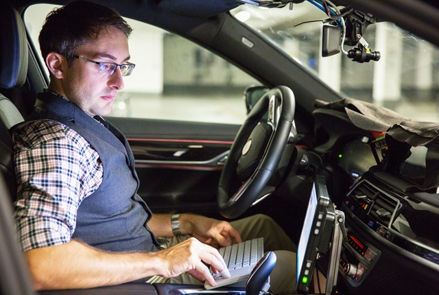 Photo of BMW engineer André Mueller testing autonomous driving technology courtesy of Intel.