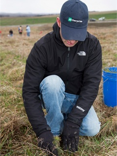 Dan Friedman, group rental manager for Enterprise, plants a tree during the event.
