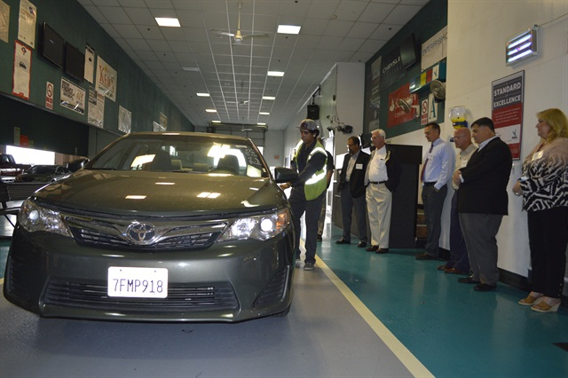 Attendees gathered for a condition report demonstration on a Toyota Camry pulled from a rental fleet. Condition reports generally average 15 minutes for rental vehicles.
